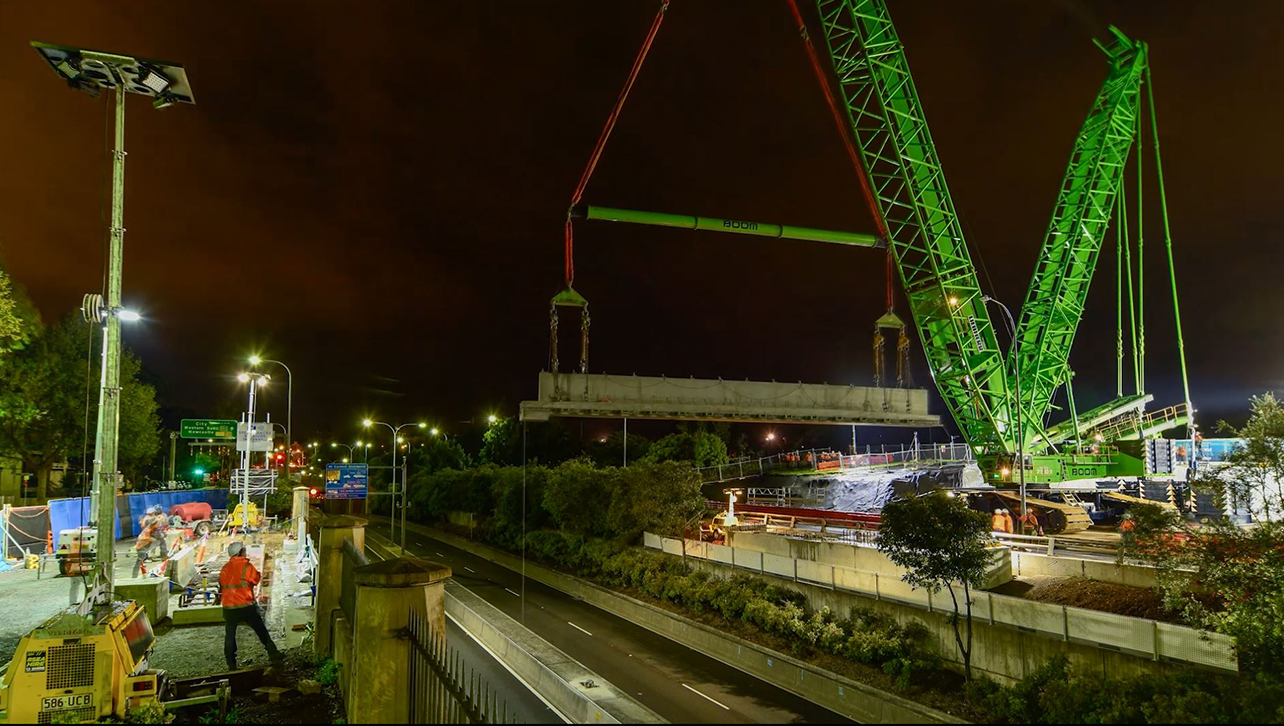 A large green crawler crane lifts a bridge girder into place over the Eastern Distributor