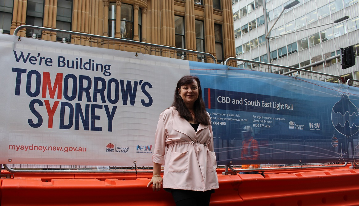 Marg Prendergast in front of CBD construction hoarding