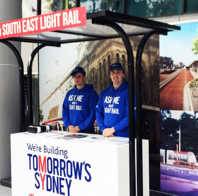 Staff standing at a mobile stall giving information about Sydney light rail