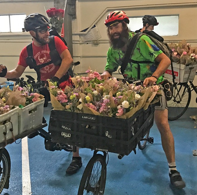 Couriers prepare to deliver bouquets of flowers by bike