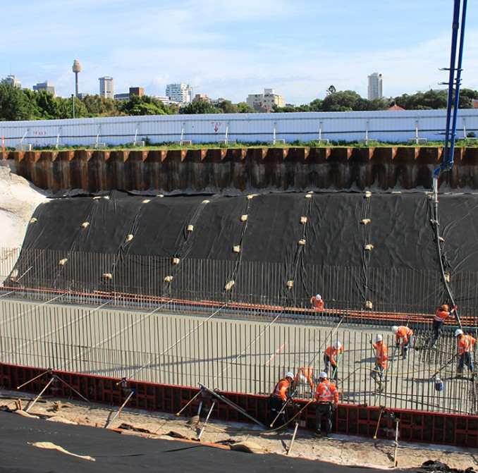 Workers pour the concrete slab that will form the base of the light rail tunnel at Moore Park.