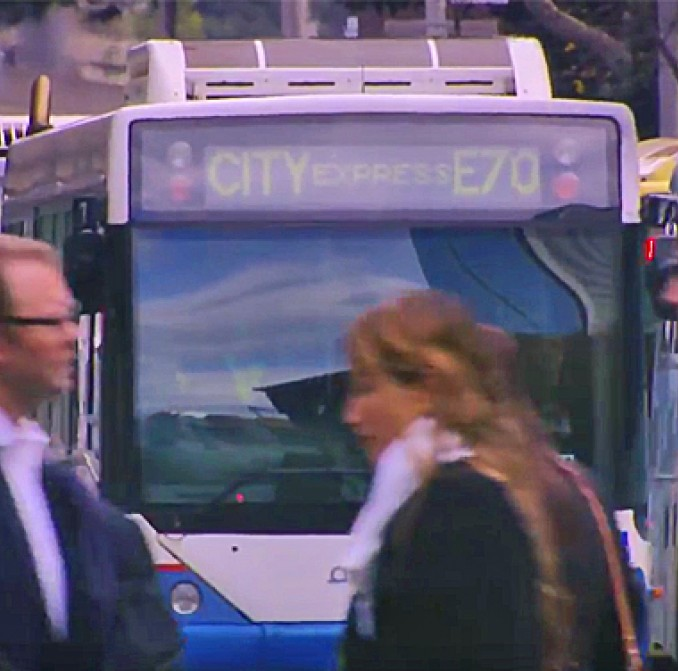 People crossing CBD road in front of buses