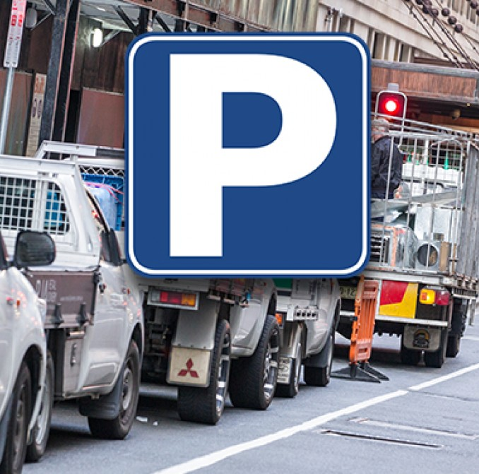 Tradie's utes parked on a CBD street and a Parking symbol