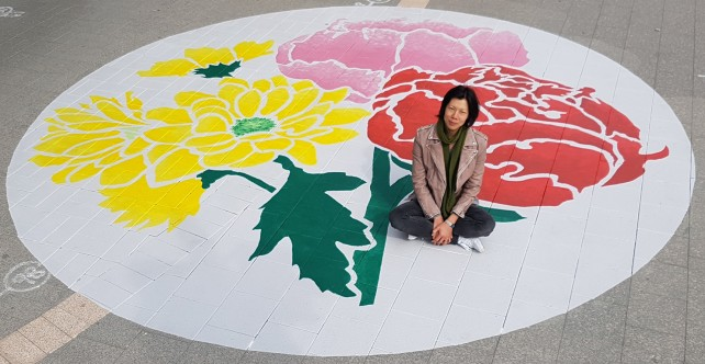 Artist Mimi Tong with her bright Chinese Enamelware painting