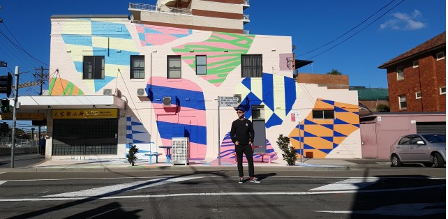 Elliott Routledge (aka Numskull) with his bold, playful mural The Playground